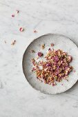 Dried edible pink rose petals on a grey plate on a white and grey marble surface