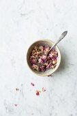 Bowl of dried edible pink rose petals and metal spoon on a grey and white marble surface