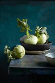 Kohlrabi in a bowl and on a wooden table