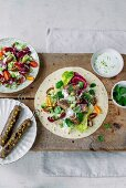 Lamb kebabs with a colourful salad, lime yogurt dressing, a tortilla and cress