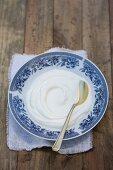Natural yoghurt on a white and blue saucer with a teaspoon