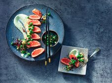 Salmon tataki coated in sesame seeds on wasabi and lime crème fraîche and pea and cucumber salad