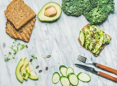 Sandwich with avocado, cucumber, kale, kress sprouts, pumpkin seeds over marble background