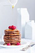 Stack of homemade american eggless chocolate pancakes with maple syrup flowing from jar