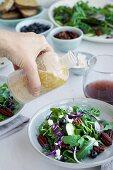 Hand pouring Toasted Walnut Sherry Feta Vinaigrette onto a Spicy Pecans Feta Arugula Salad