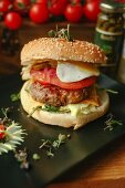 A cheeseburger with tomato and a fried egg
