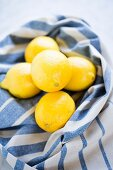 Fresh lemons on a blue and white striped tea towel