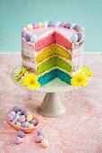 A rainbow cake decorated with mini chocolate eggs and flowers for Easter (with a slice cut out)