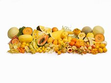 Yellow fruit and vegetables in front of a white background