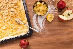 Crumble being spooned onto an apple tray bake