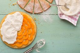 A layered mandarin cake being covered in whipped cream