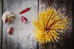 Stillleben mit Bündel Spaghetti, Knoblauch und Chili (Aufsicht)