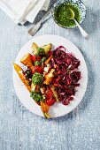 Oven baked vegetables with pesto and a red cabbage salad (top view)