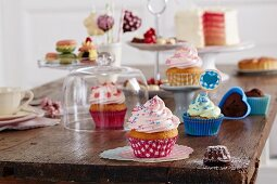 Different cupcakes, small pastries and cakes on a wooden table