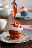 Strawberry sauce dripping from a spoon onto a cupcake with white frosting