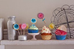 Cupcakes, paper cases and colourful decorations on a kitchen shelf