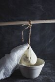 Ricotta in a cheesecloth hanging from a wooden stick and draining into a bowl