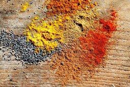Verschiedene Gewürze und Mohn auf Holzfläche