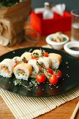 Sushi rolls with salmon, fresh cheese and cocktail tomatoes