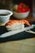 Nigiri sushi with shrimp on a black plate