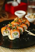 Sushi rolls with salmon, avocado, fresh cheese and herbs