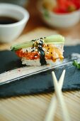 Nigiri sushi with white fish and cucumber on a black plate
