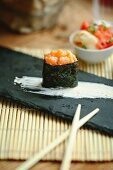 Single sushi with salmon tartare on a black plate