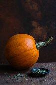 An orange pumpkin for Halloween and pumpkin seeds