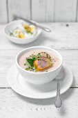 Horseradish creme soup with two slices of sausage and potato pate