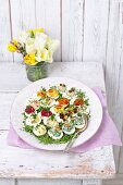 Eggs filled with different flavoured yolks on a bed of cress on a large plate