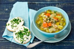 Minestrone with leeks and beans, with bread rolls topped with fresh cheese