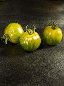 Drei grüne Tomaten der Sorte Green Zebra