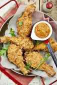 Crispy chicken legs coated in breadcrumbs with peanut sauce