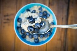 Spoon of overnight oats with blueberries, close-up
