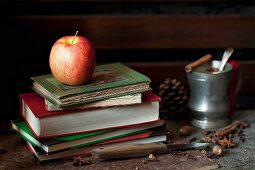 A Pink Lady apple on a pile of old books with mulled apple juice