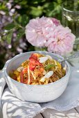 Singapore noodles with yellow pepper, chilli and shoots on a table outdoors