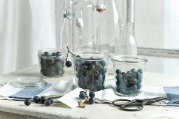 Blackthorn fruits in storage jars on a kitchen table with a blackthorn branch and scissors