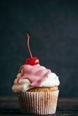 A homemade cupcake topped with a cocktail cherry