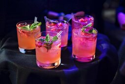 Tray of rasberry, mint, vodka cocktails being served at an event