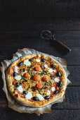Mozzarella and cherry tomatoe pizza served on the wooden background