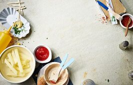 Ingredients for fast food or streetfood (raw potato sticks, ketchup, mustard)