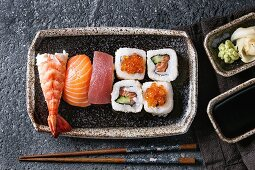 Sushi Set nigiri and sushi rolls in dark ceramic plate with soy sauce and chopsticks over black stone texture background