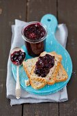 Homemade blackberry and blueberry jam in a glass and on a slice of bread