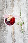A mini smoothie bowl in a cup with berries and popped amaranth