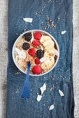 A cacao smoothie bowl with berries, banana, coconut chips and popped amaranth