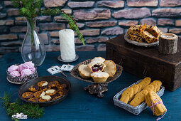 A Christmas table laid with various Christmas cakes and biscuits