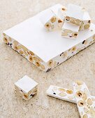White nougat with nuts on a stone background