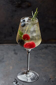 A cocktail with fresh berries and mint