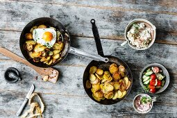 Colourful fried potato dishes (classic fried potatoes, radish quark, herb cream and marinated crab, and fried potatoes with a fried egg)