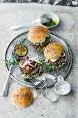 A burger with pork, rocket, eggplant, and dried tomatoes